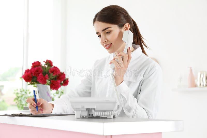 Beauty salon receptionist talking on phone. At desk royalty free stock photos