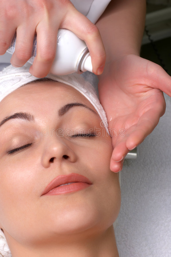Beauty salon series, hydration before cleaning. Woman getting extra hydration procedure before skin cleaning at beauty salon stock image