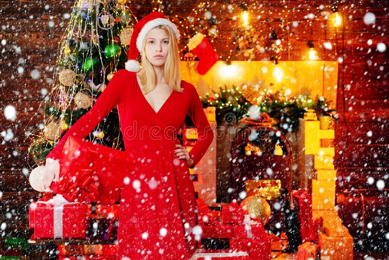 Beauty Santa girl. Fashion girl with Christmas present box. Girl is happy about the new year. Woman in evening dress stock photo