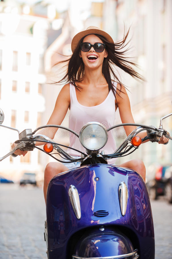 Beauty on scooter. Excited young and beautiful woman riding scooter along the street and keeping mouth open royalty free stock photo