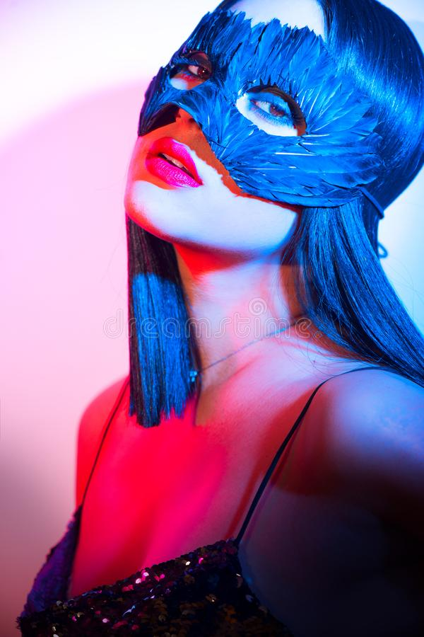 Beauty brunette woman portrait. Girl wearing carnival black feather mask. Black hair, red lips, holiday makeup royalty free stock photo