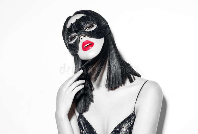 Beauty brunette woman portrait. Girl wearing carnival black feather mask pointing hand, proposing products. Beauty brunette woman portrait. Girl wearing carnival stock images