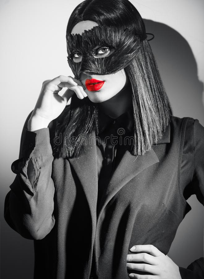 Beauty brunette woman portrait. Girl wearing carnival black feather mask pointing hand, proposing products. Beauty brunette woman portrait. Girl wearing carnival royalty free stock photography
