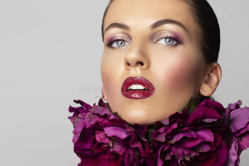 Beauty Girl with flowers wreath. Beautiful young woman perfect make-up red lips. Trendy makeup beauty and spa skin concept royalty free stock photos