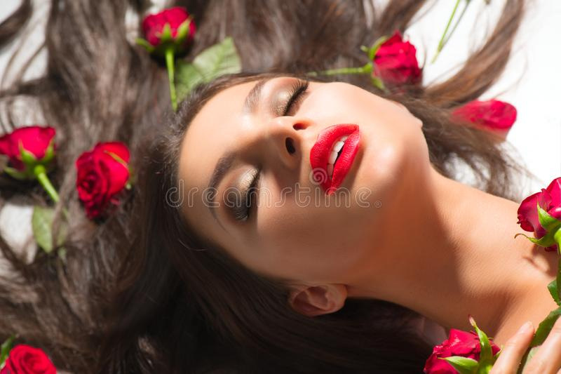 Beauty Sexy Model girl lying on white background with red rose flowers in her hair. Beautiful brunette young woman with long hair royalty free stock photography