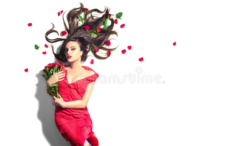 Beauty Sexy Model girl lying on white background with red rose flowers in her hair. Beautiful brunette young woman with long hair. And perfect make-up, red royalty free stock image