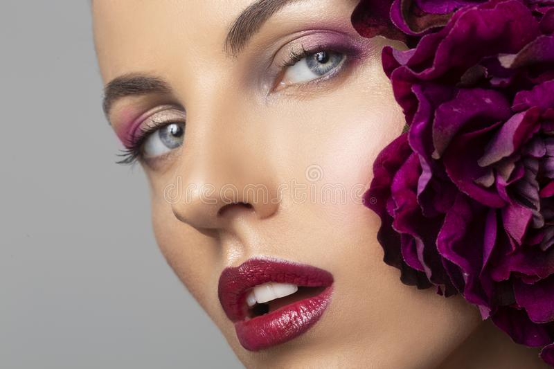 Beauty Model girl with perfect make-up, red seductive lips. Beautiful young woman with flowers, Beauty and spa skin concept royalty free stock photo