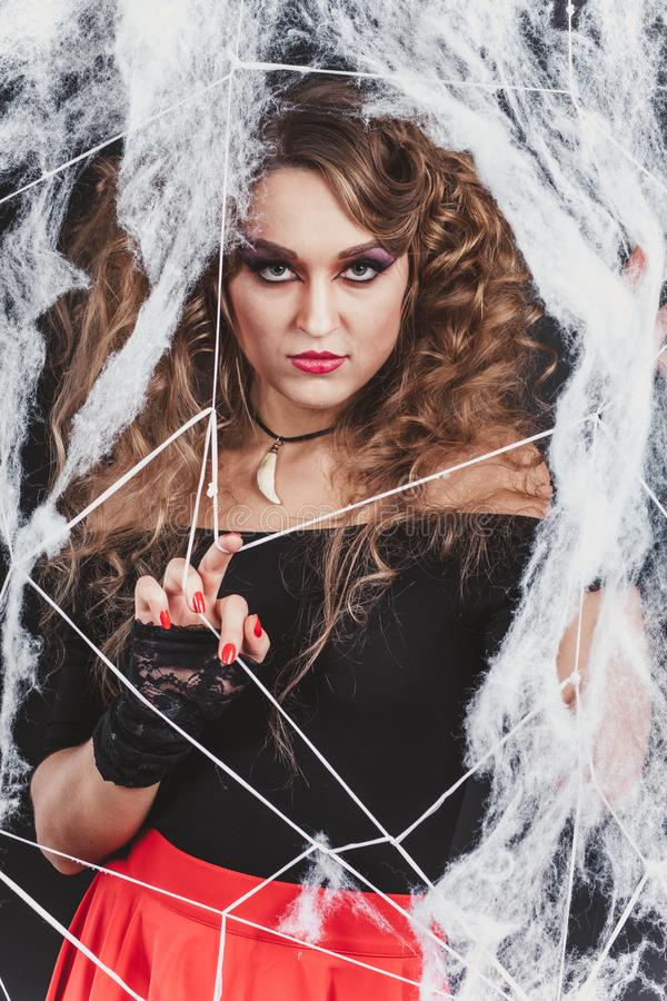 Beauty Witch girl caught in a spider web. Fashion Art design. Beautiful Gothic model girl with Halloween make up stock photography