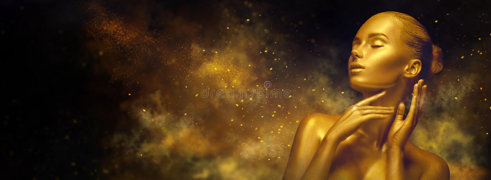 Beauty sexy woman with golden skin. Fashion art portrait closeup. Model girl with shiny golden professional makeup. Over holiday blinking background. Gold stock image