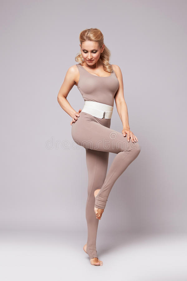 Beauty woman sport yoga pilates fitness body shape clothes. Beautiful blonde woman perfect athletic slim figure engaged in yoga, exercise or fitness, lead royalty free stock photos