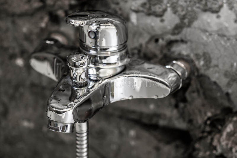 Beauty of shiny metal chrome surface on a bathroom tap with water drops on it and concrete wall background as modern interior stock photography