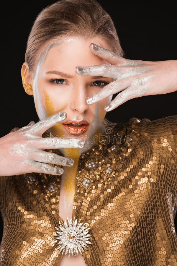 Beauty shoot of fashionable blonde woman with gold and silver pa. Beauty shoot of fashionable blonde lady with gold and silver paint on her face and hands royalty free stock photo
