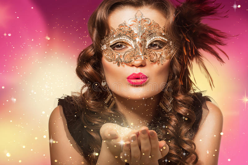Beauty shoot of smart brunette woman in carnival mask. Over colored background and sparkles. Evening makeup and dark curly hairs royalty free stock photo