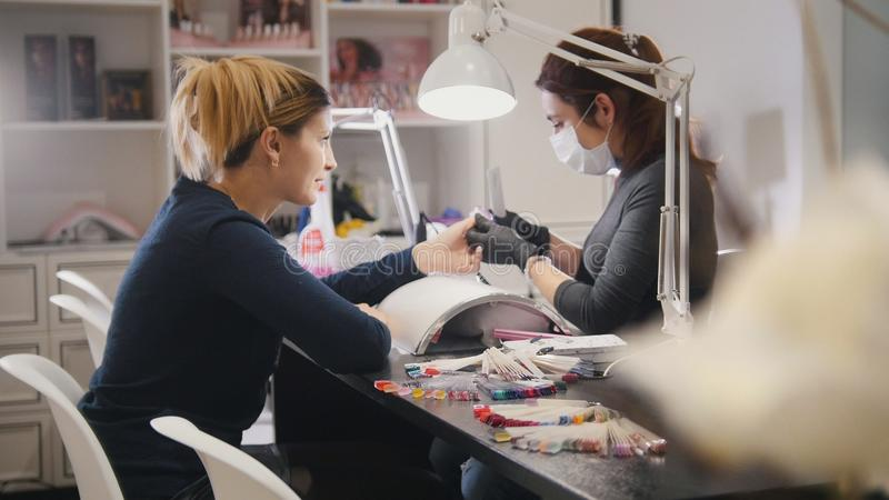 Beauty shop - nail master in doing professional manicure for white model - close up stock photo