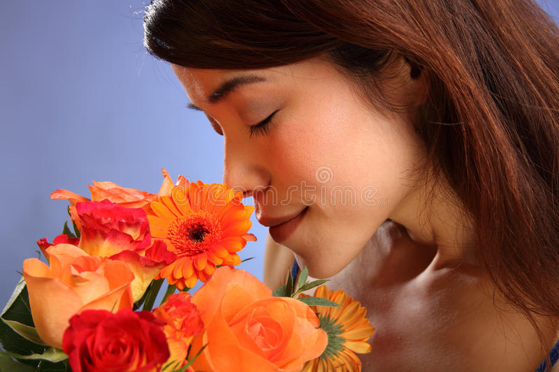 Beauty shot young Japanese girl smelling flowers. Flowers for you. Beauty shot of stunning young Japanese girl smelling a bunch of flowers, including roses royalty free stock photos