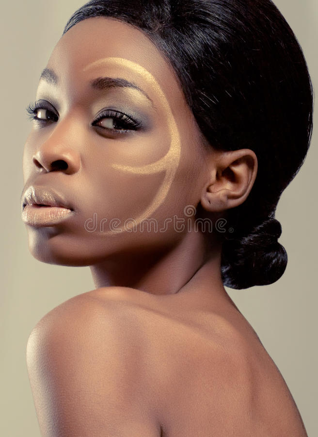 Beauty shot of a young woman with golden makeup royalty free stock images