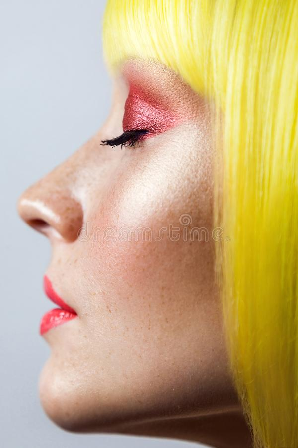 Beauty side view profile portrait of calm cute young female model with freckles, red makeup and yellow wig, closed eyes with royalty free stock photography