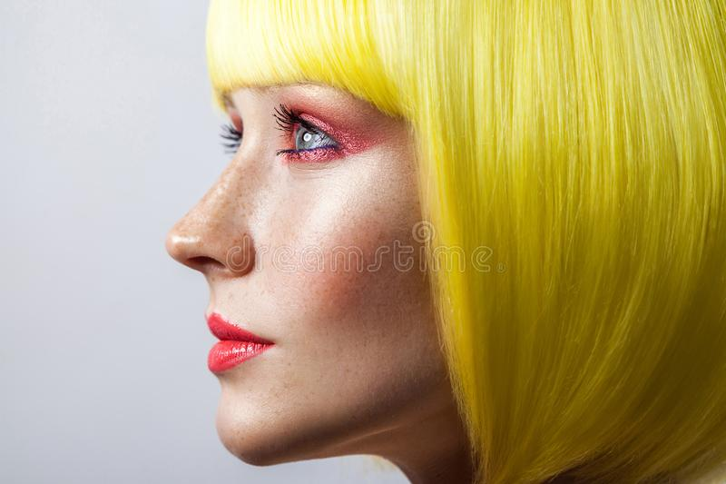 Beauty side view profile portrait of cute young calm female model with freckles, red makeup and yellow wig, looking forward with royalty free stock photo