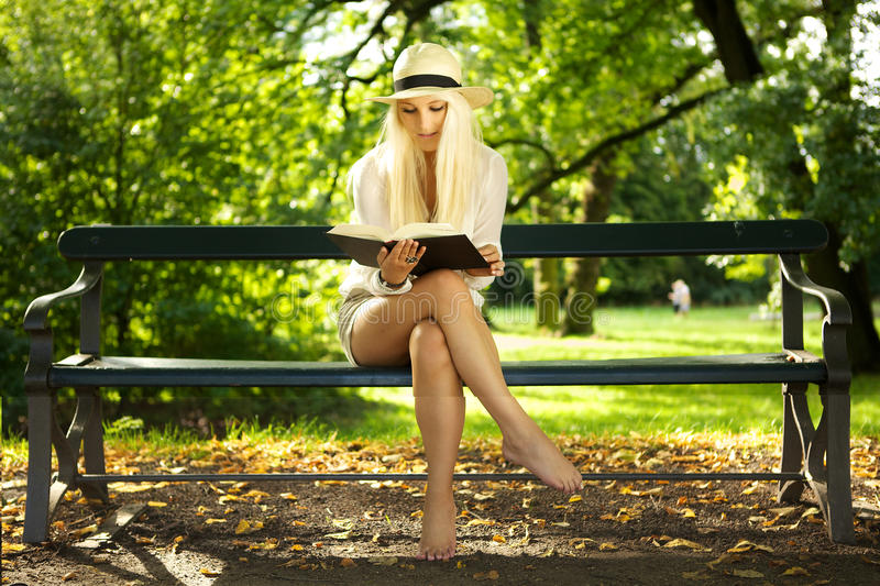 Download Beauty Sitting On A Bench Reading In The Sun Stock Photo - Image: 21469404