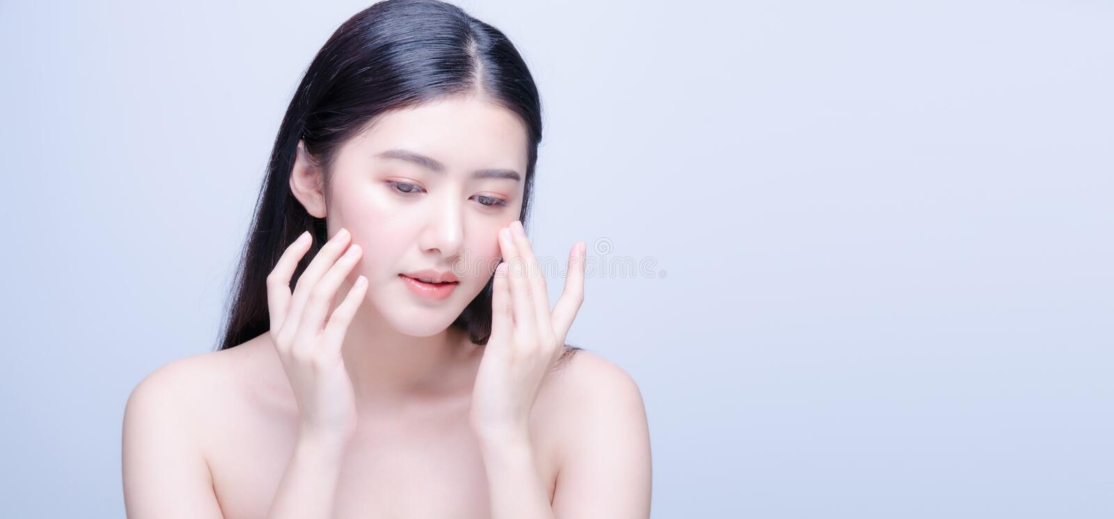 Beauty skin care asian woman smile to you isolated on blue background. Face, eye, model, pretty, attractive, chinese, clean, copy, copyspace, cosmetics, cute royalty free stock images