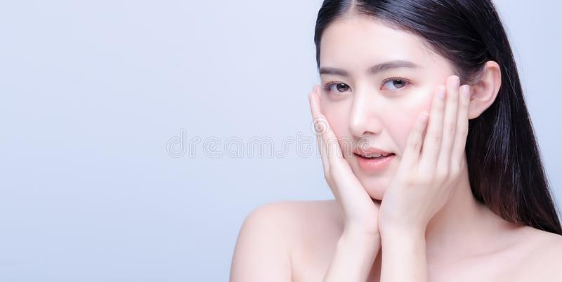 Beauty skin care asian woman smile to you isolated on blue background with shy emotional. Face, eye, model, pretty, attractive, chinese, clean, copy, copyspace stock photography