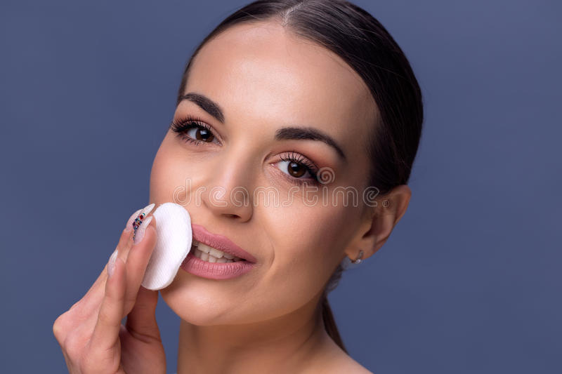 Beauty skin care. Beautiful happy woman removing face makeup using cotton pad. Close up portrait of healthy smiling female model. stock photos