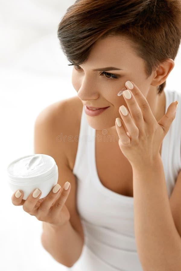 Beauty Skin Care. Beautiful Woman Applying Cosmetic Face Cream royalty free stock photo