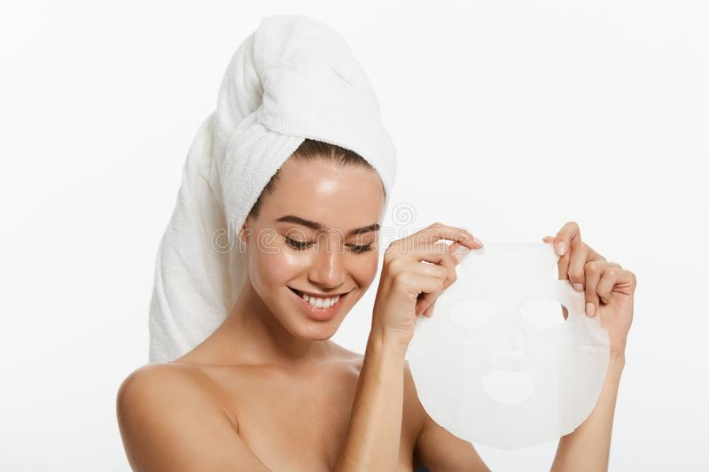 Beauty Skin Care Concept - Beautiful Caucasian Woman applying paper sheet mask on her face white background. stock photos