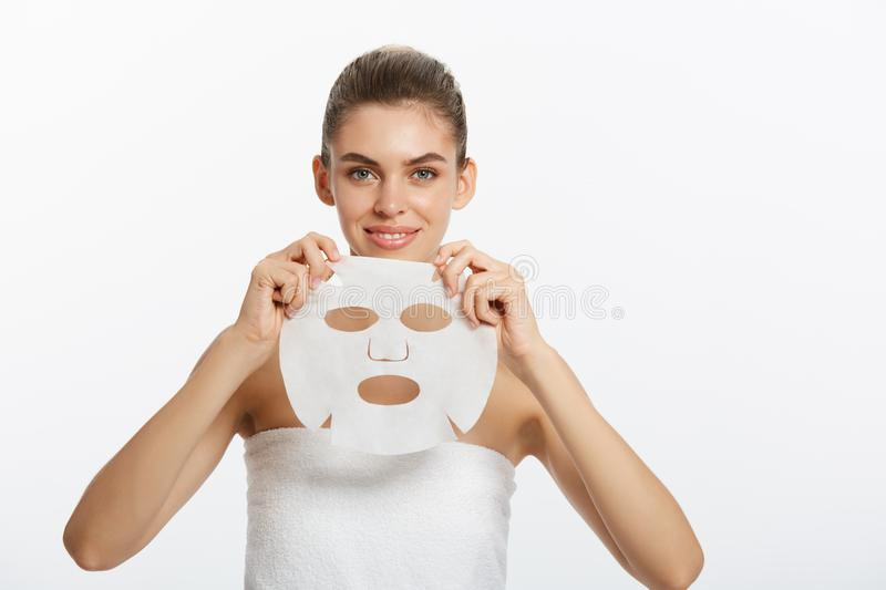 Beauty Skin Care Concept - Beautiful Caucasian Woman applying paper sheet mask on her face white background. stock photography