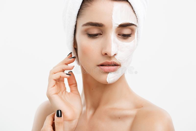 Beauty skin care concept - beautiful caucasian woman face portrait applying cream mask on her facial skin white royalty free stock image