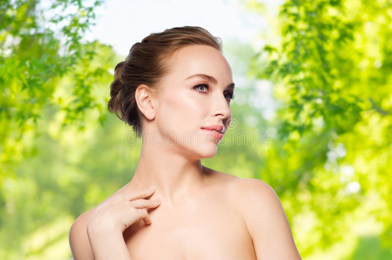 Beautiful young woman touching her neck stock photo
