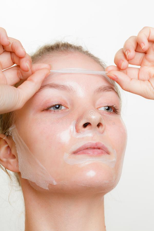 Woman removing facial peel off mask royalty free stock image