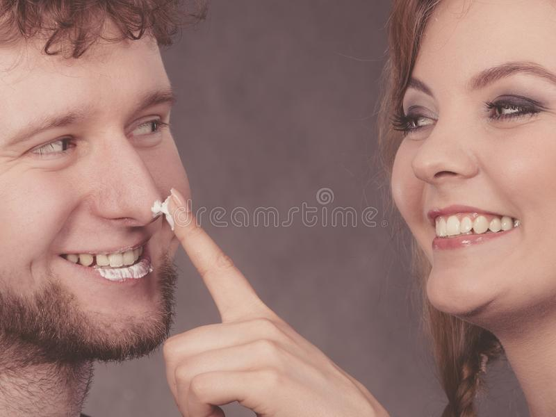 Young couple fooling with cream royalty free stock images