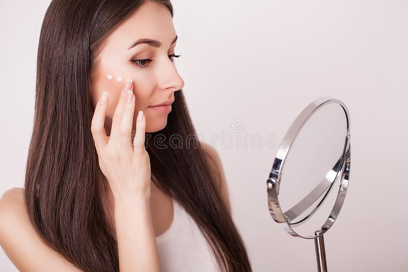 Beauty, skin care and people concept - smiling young woman applying cream to face and looking to mirror at home bathroom stock photo