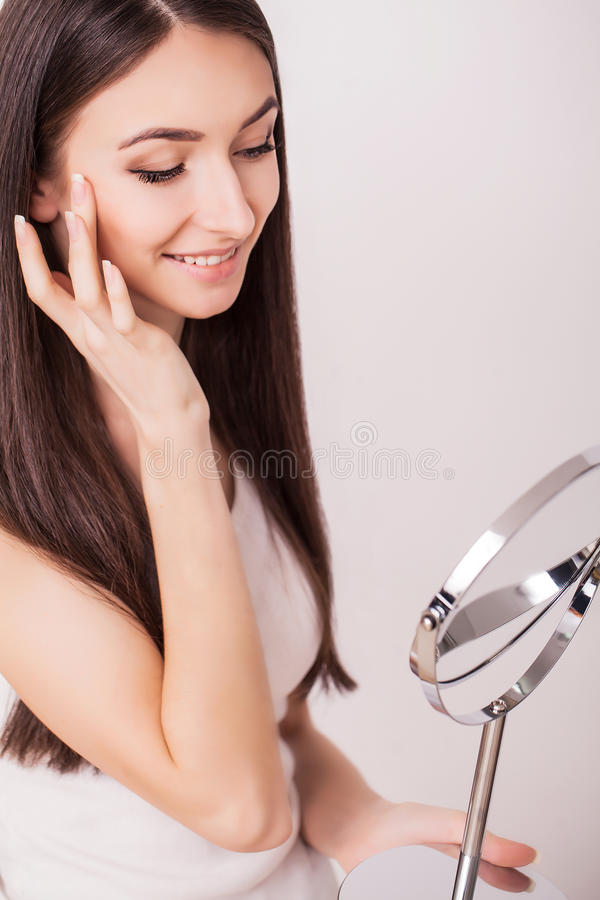 Beauty, skin care and people concept - smiling young woman applying cream to face and looking to mirror at home bathroom stock images