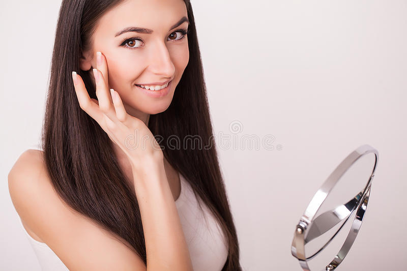 Beauty, skin care and people concept - smiling young woman applying cream to face and looking to mirror at home bathroom.  stock photos