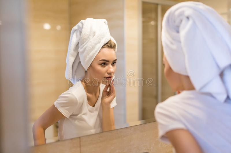 Beauty, skin care and people concept. Smiling young woman washing her face with facial cleansing sponge at bathroom. Beauty, skin care and people concept royalty free stock images