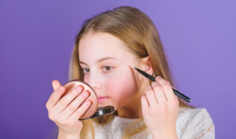 Beauty is but the skin deep. Beauty look of little makeup model. Small beauty model. Adorable beauty artist looking in. Glass and applying makeup royalty free stock photos
