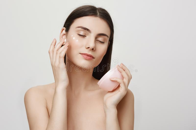 Beauty and skincare concept. Studio portrait of gentle good-looking european woman rubbing in facial cream, enjoying royalty free stock image