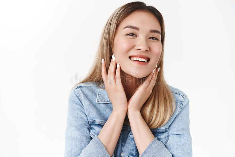 Beauty, skincare, wellbeing, diversity concept. Attractive cheerful tender young asian blond girl take care skin touch royalty free stock photo