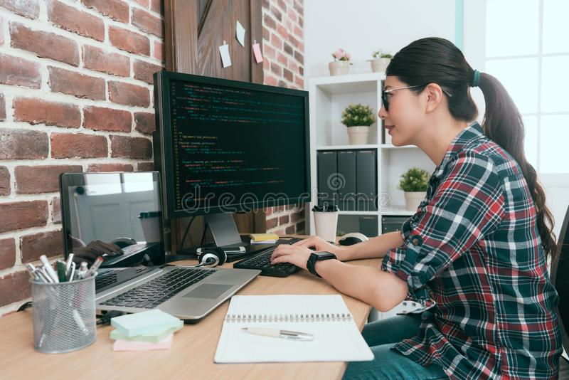 Beauty smiling female programmer using computer. Working in office and typing data code to developing new system protection online user security royalty free stock photo