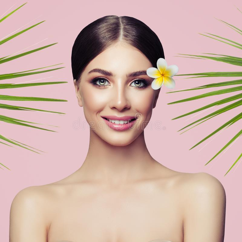 Beauty smiling spa model with natural make up and green leaves stock photo