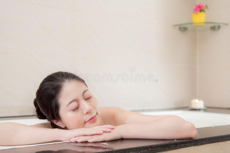 Smiling woman feeling tired leaning on bathtub royalty free stock photo