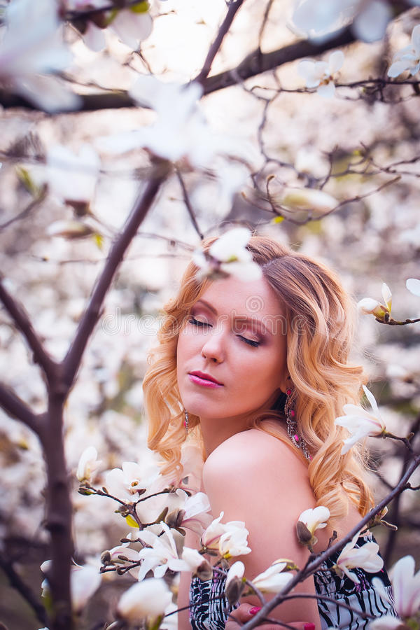 Beauty smiling woman near white magnolia royalty free stock image