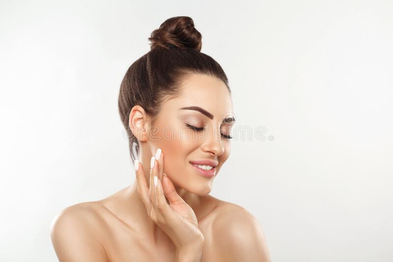 Beauty and Spa Concept. Beautiful Young Woman with Clean Fresh Skin touch face. Facial treatment. Girl Female With Natural Makeup. Cosmetology. Skin Care stock photo