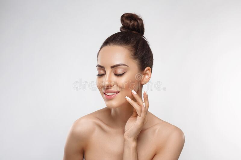Beauty and Spa Concept. Beautiful Young Woman with Clean Fresh Skin touch face. Facial treatment. Girl Female With Natural Makeup. stock image
