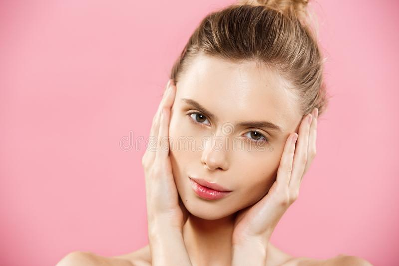 Beauty Spa Concept - Caucasian Woman with perfect face skin Portrait. Beautiful Brunette Spa Girl showing empty copy. Space. Isolated on pink studio background royalty free stock images