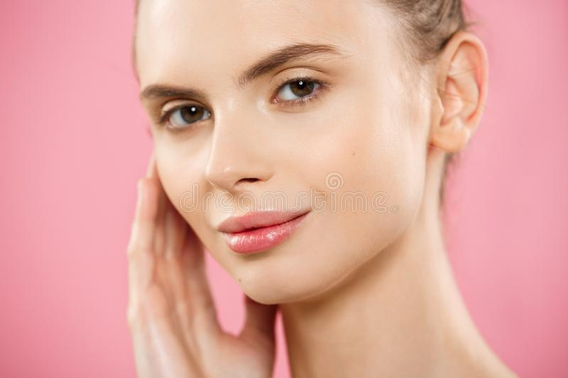 Beauty Spa Concept - Caucasian Woman with perfect face skin Portrait. Beautiful Brunette Spa Girl showing empty copy. Space. Isolated on pink studio background stock photos