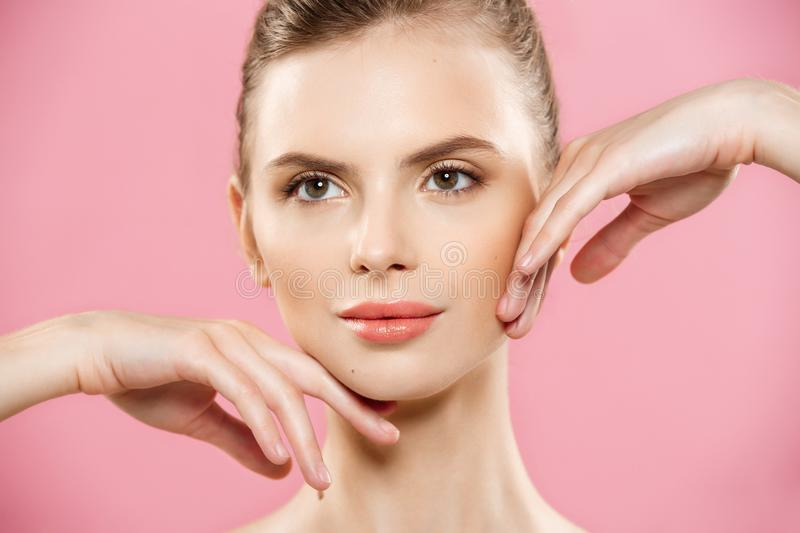 Beauty Spa Concept - Caucasian Woman with perfect face skin Portrait. Beautiful Brunette Spa Girl showing empty copy. Space. Isolated on pink studio background royalty free stock photo