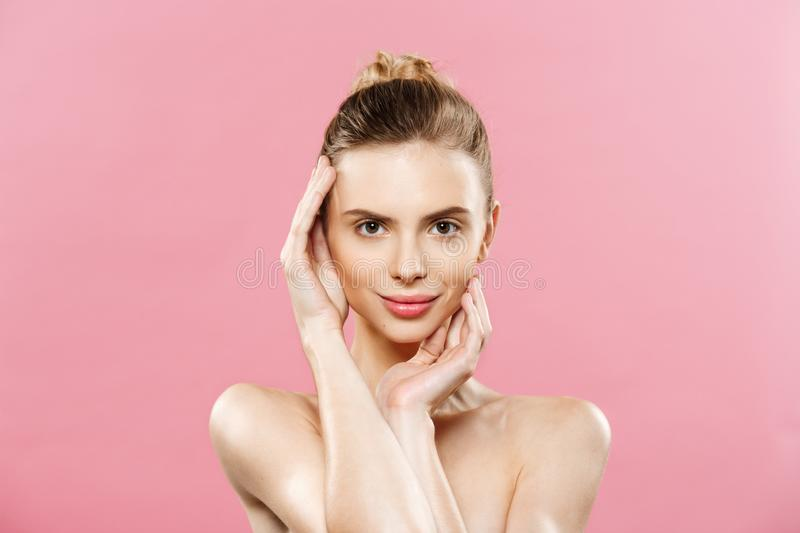 Beauty Spa Concept - Caucasian Woman with perfect face skin Portrait. Beautiful Brunette Spa Girl showing empty copy. Space. Isolated on pink studio background royalty free stock photos